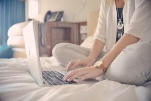 ベッドでネットショッピングをする女性